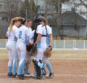 The softball team huddles during a game last season. The Lasers have a new coach and look forward to a new season.  (Photo by Tom Horak)