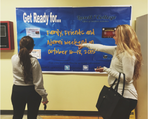 Photo by Megan Sapienza Students check out the Spirit Week and Family, Friends, and Alumni Weekend schedule posted in the Campus Center.