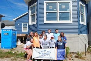 Photo courtesy of Katie Rathbun The LSTY group poses for a picture in front of a home they spent time working on during their trip.