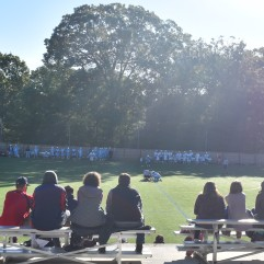 Parents and fans watch a face-off in the men's alumni lacrosse game. Photo by Jackie Colombie.