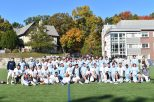 Men's lacrosse (blue) and men's alumni lacrosse (white) pose for a photo on Grellier Field. Photo by Jackie Colombie.