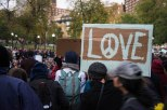 """One protestor holds a """"Love"""" sign with the peace symbol."""
