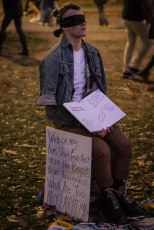 A blindfolded protoster sits in Boston Common with a book for people to write in.
