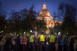 Police monitor a group of peaceful protestors in front of the State House as the night grows dark.