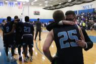 The Lasers weren't able to hold on and lost the final game 101-83 to the Falcons. Junior forward Ryan Jones (right) is consoled while teammates look on at the game. (Photo by Tom Horak)
