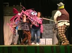 Spencer Koisor as Shrek (right) battles the Dragon handled by several students (left).