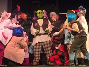 Numerous fairy tale creatures surround Spencer Koisor as Shrek (center).
