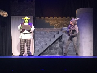 Spencer Koisor as Shrek (left) and Taylor Powell as Donkey (right) meet for the first time in character on stage.