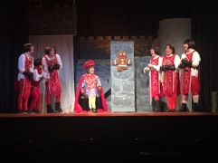 Gregg Cazzaza as Lord Farquadd (center left) interrogates Sara Bayles as the Gingerbread Man (center right) while students playing the royal guards surround them.